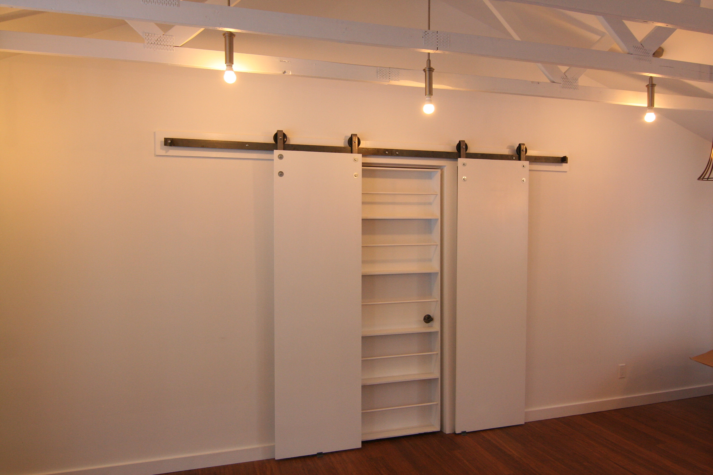 Same idea with the hangers mounted on the other side of the doors.  This is the biparting system used here for a shelving unit.