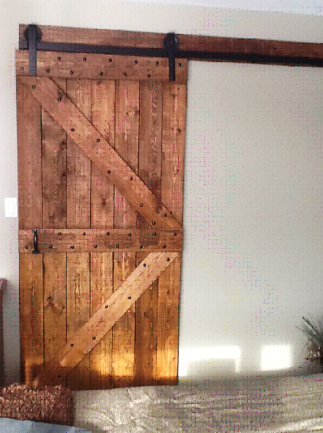Our client from up north sent us this photo of his door installation using the Heavy Metal barn door hardware.  He made the door himself!