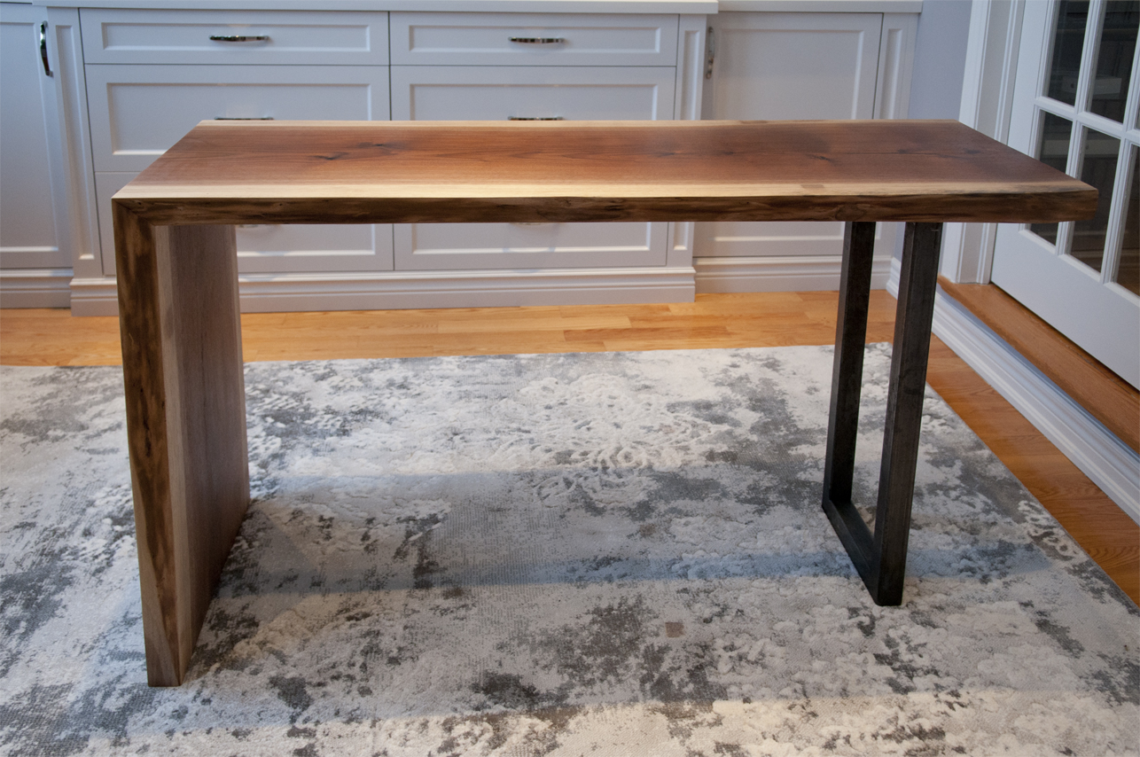 Set against the white built-in cabinetry and the grey tones rug, the walnut desk with raw steel legs really pops.