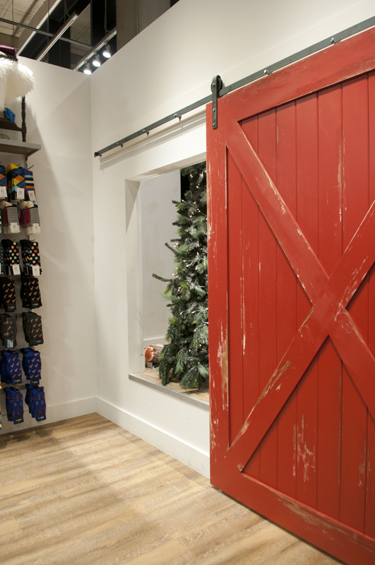 This distressed red barn door on the Heavy Metal hardware covers up the access opening of the display window.