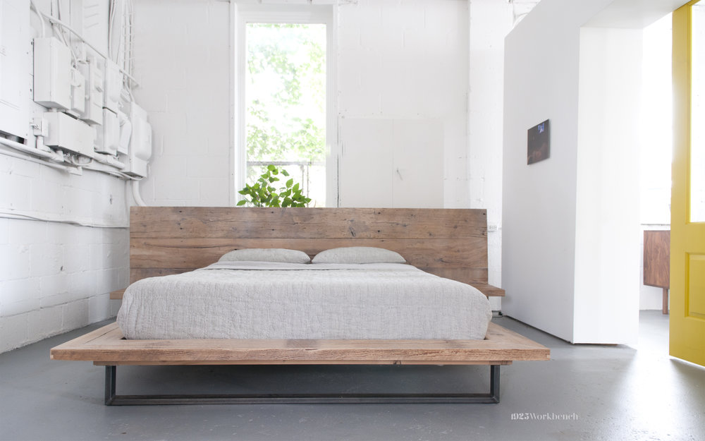 Here is our platform bed inside made of reclaimed wood. The left wall are electrical panels from the machine shop before us. we decided to leave them on the wall and paint them all white as an installation and to reclaim a piece of the building's history.