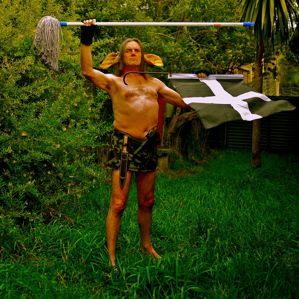 Man of Curnow - at the request of Andre Stitt. With Cornish Flag, Mach 10 machine pistol, pig sticker, and Floor Mop. 2012.        2m X 2m archival photograph.