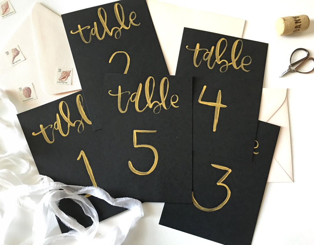 Gold and black brush calligraphy table numbers