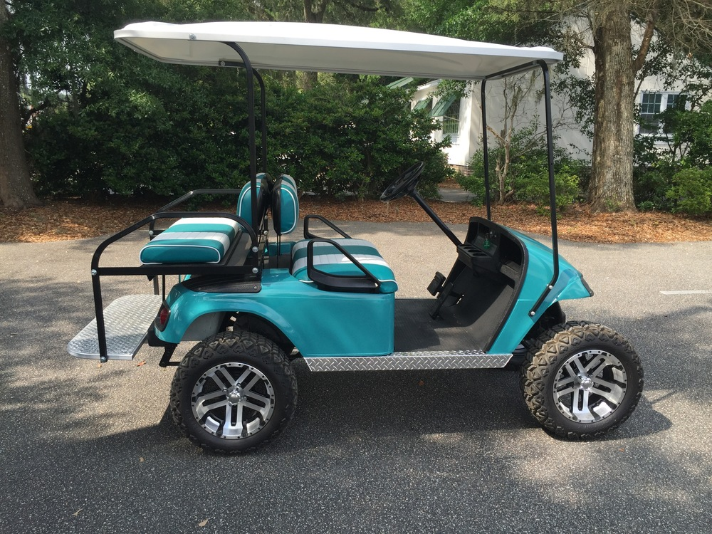 Teal EZGO Lifted Cart Teal/white seats, white extended top, new batteries, high speed code, LED lights, Backlash (23x10x14) tires, and state of charge meter