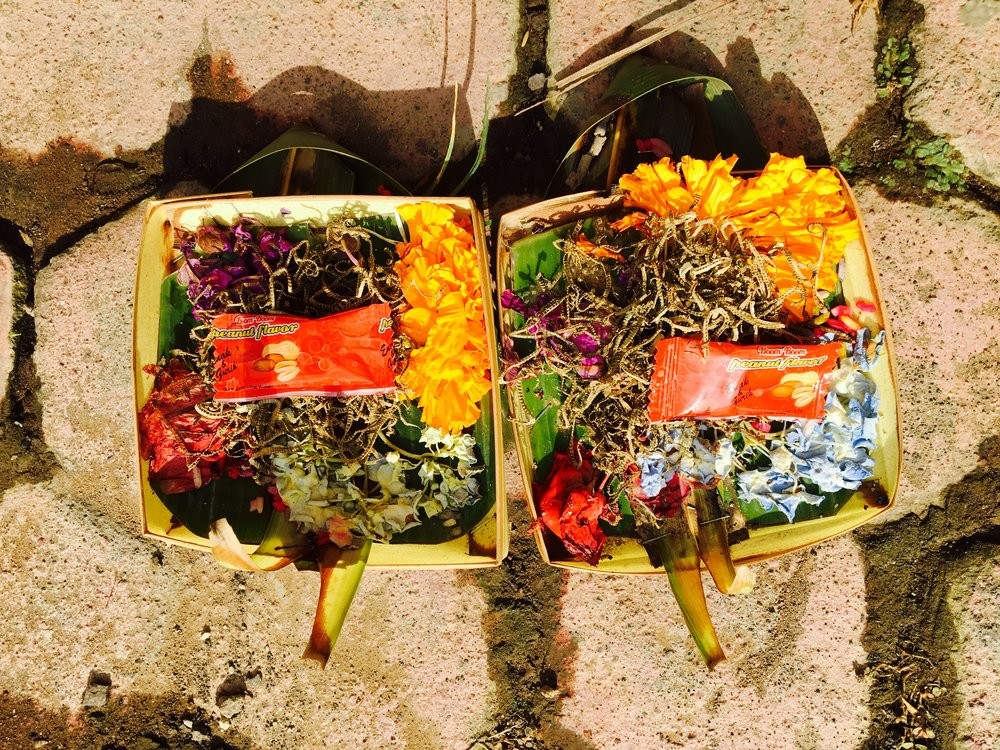 Offerings- that I keep stepping on. Pretty trays of loveliness litter the pavements.