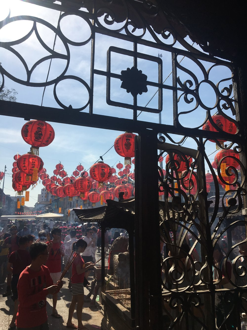 A temple at Chinese New Year which was rich with incense, fire crackers and people tussling for little red envelopes.