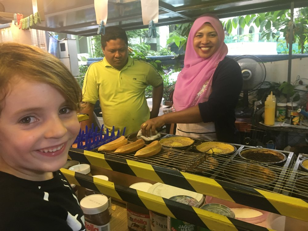 The youngest watching intently as the kind lady makes him Apam Balik, a Malaysian pancake taco filled with nutella and peanuts. It was delicious but so sugary!