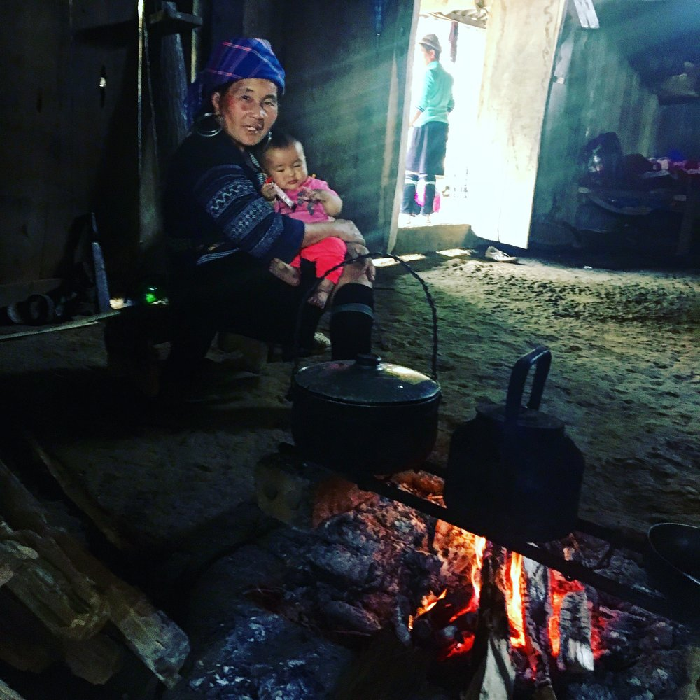 Grandmother with baby by the fire, waiting for the water to boil for the rice.