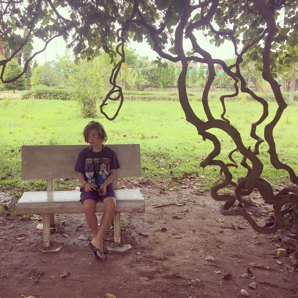 The eldest, in quiet contemplation at the killing fields (Cheung Ek) listening to the audio guide.
