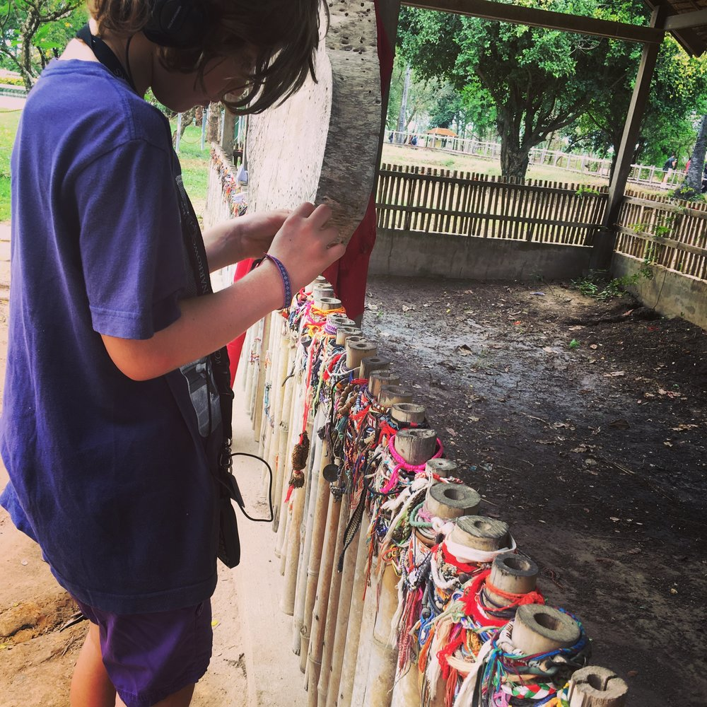 Placing our bracelets as a sign of respect at the site of a mass grave in the Killing Fields.