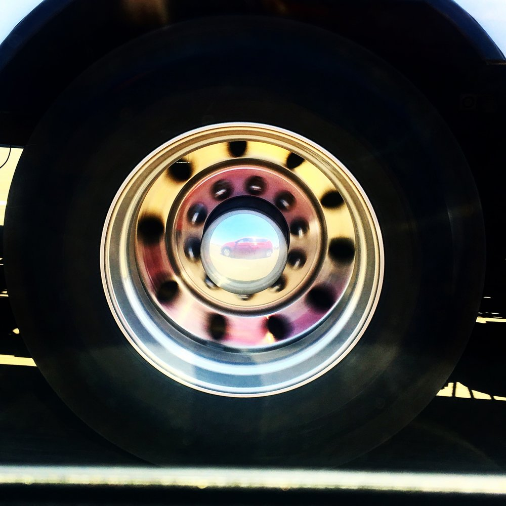 A truck's hub cap view of our car.