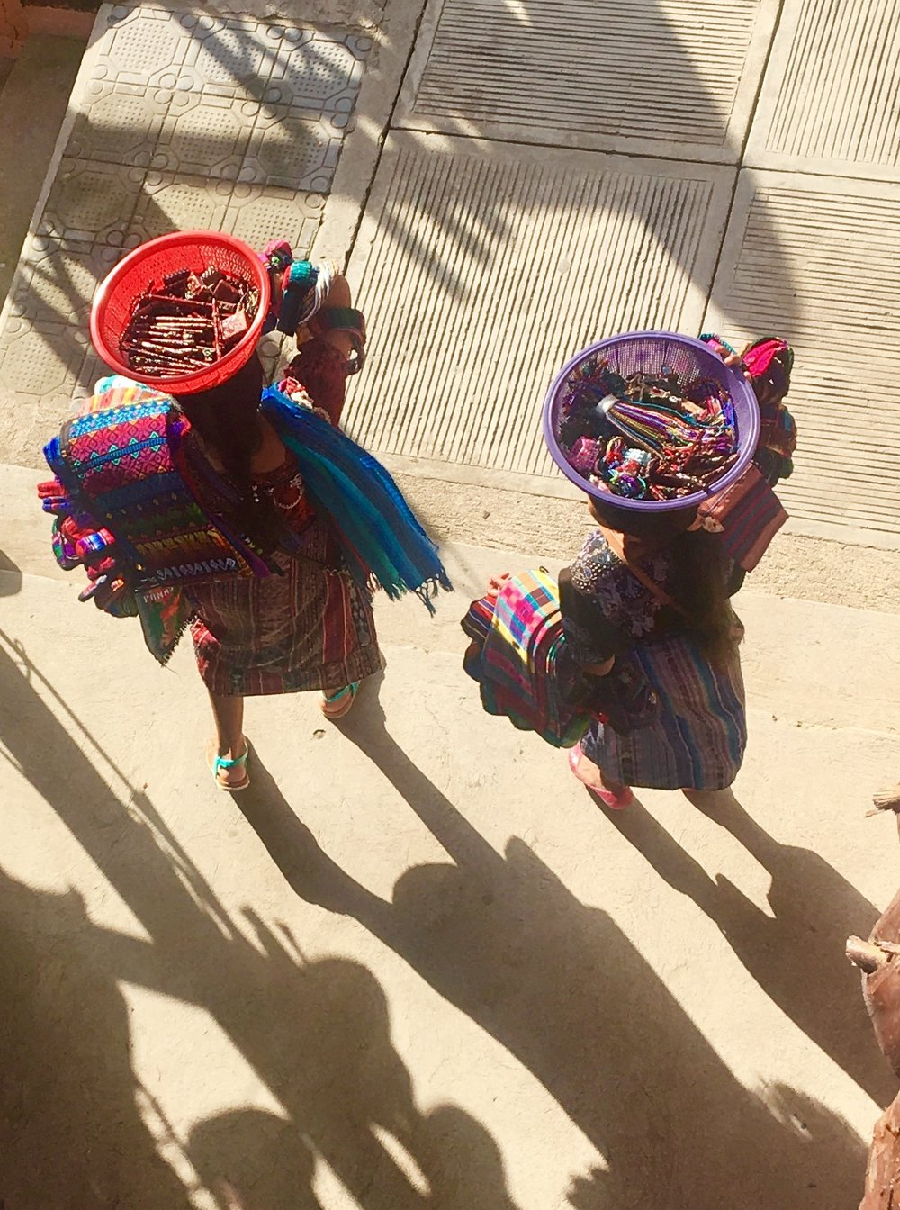 Women, carrying baskets on their heads.