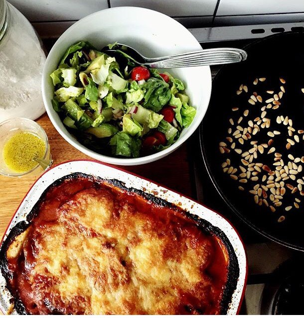 An Italian melanzane accompanied by a green salad with toasted pine nuts