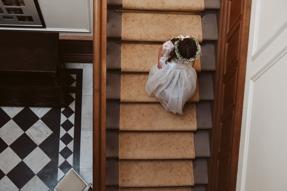 Flower girl makes her way down the grand staircase