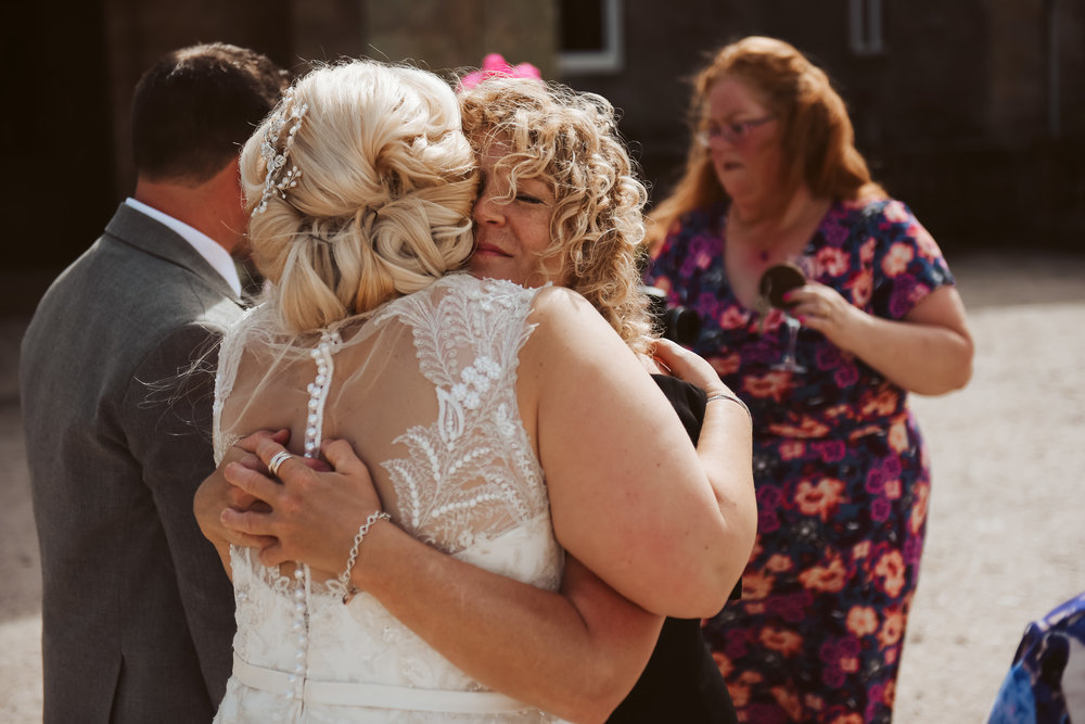 Wedding guests hugging bride