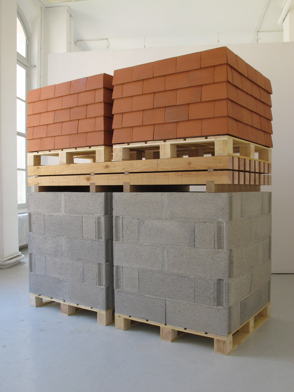 La Maison     2014, pallet, breeze blocks, mortar, rafters, tiles, 210x 210 x 100 cm    A minimal house. The materials that I chose are strictly necessary for habitat building. Here, the materials are presented in their storage condition, rack and pallet. Nevertheless, they experienced a mutation. The materials have anticipated their future, their conditioning doesn't consider their use.   La Maison   is achieved.     A house represents comfort, refuge, protection. Here it is massive, compressed and impenetrable.