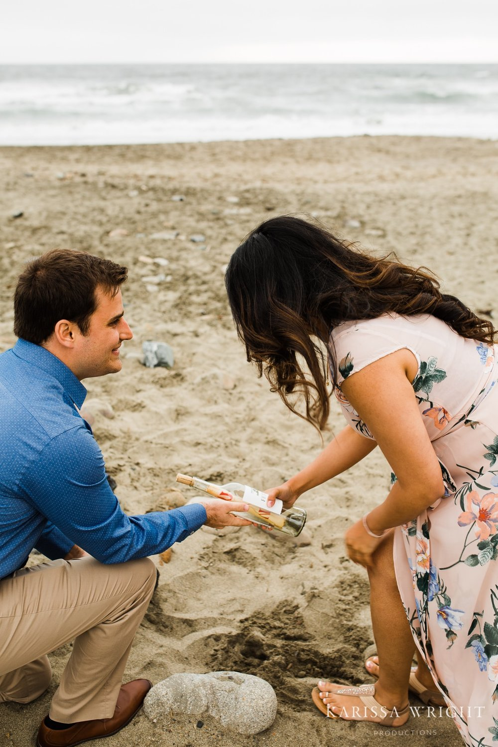 Alex is kneeling down on the sand of the Pacifica State Beach handing Lipika a wine bottle that has a note.