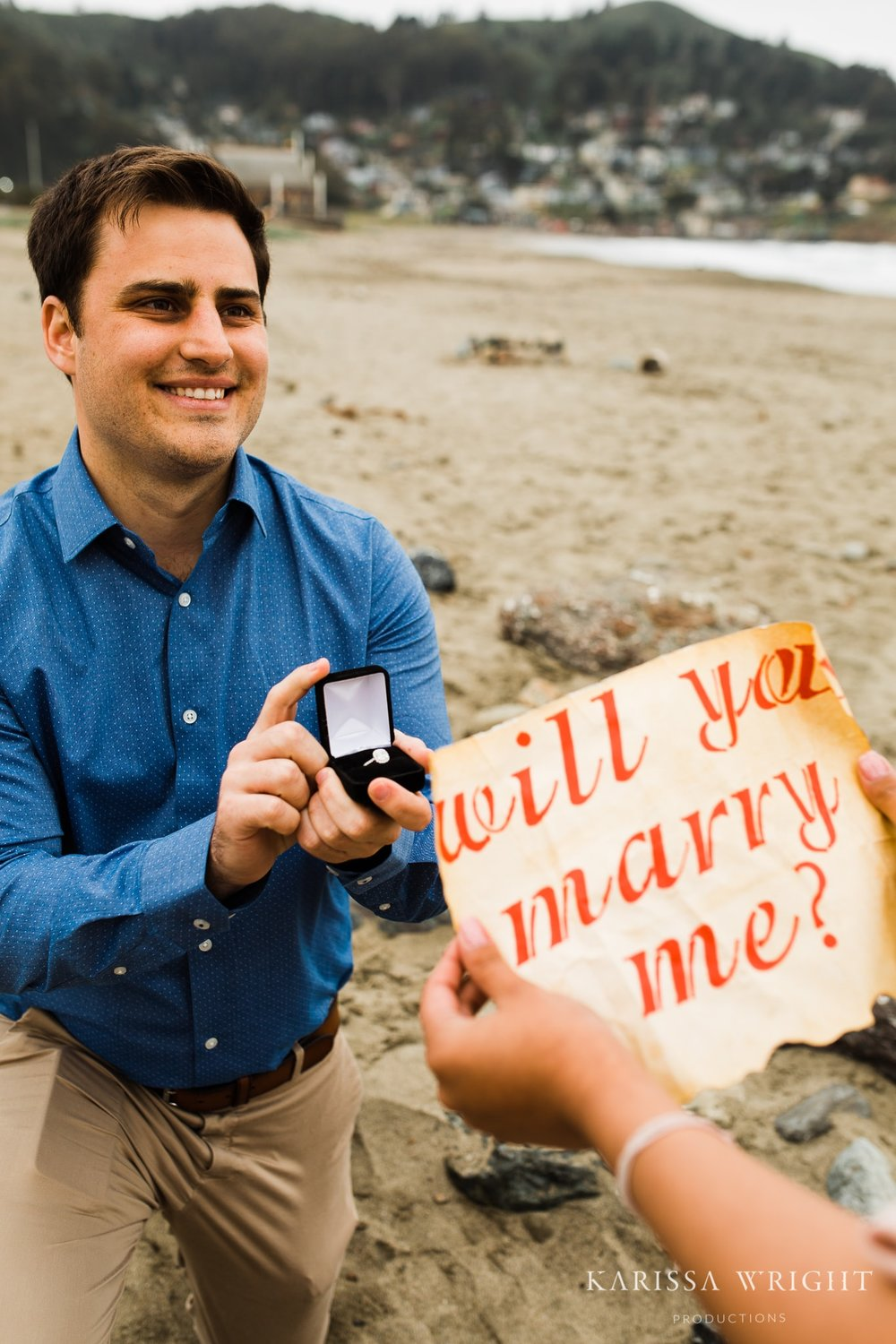 "Alex is on one knee with the engagement ring in a box opened while Lipika looks at the note that says ""Will you marry me?"" in calligraphy."