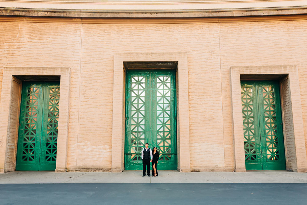 Derick and Christine pose in front of San Francisco's Palace of the Fine Arts on a beautiful cloudy and sunny day. The three green doors brought in a beautiful reflection of the cloudy skies on their engagement session to announce their wedding celebration.