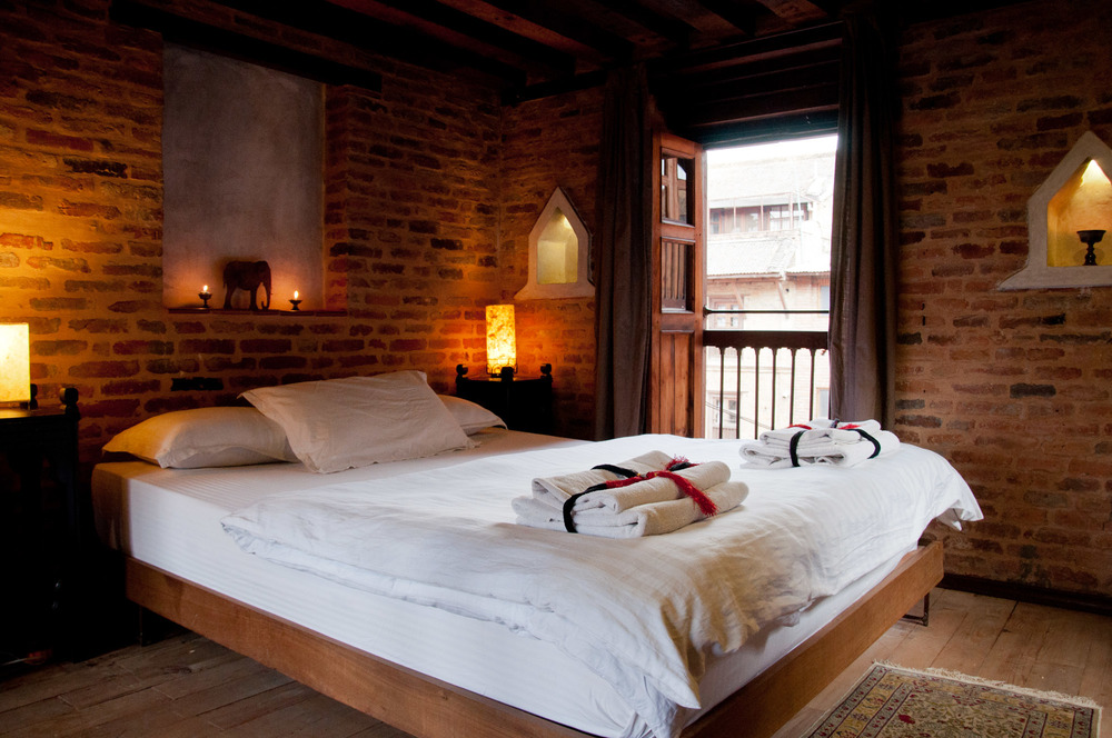 Comfortable queen size bed with sets of towels. View over the front courtyard.