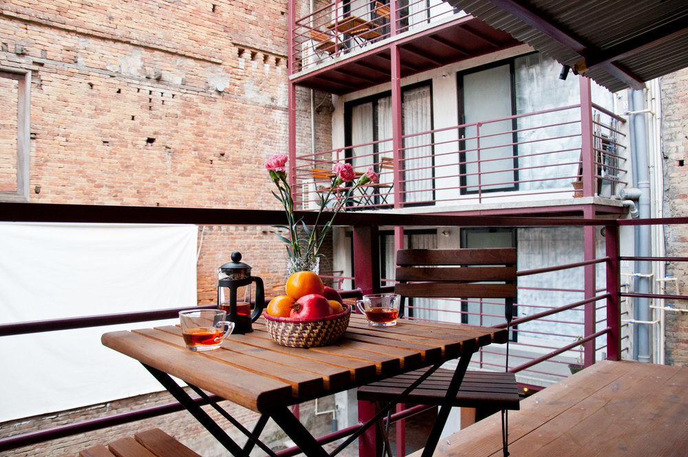 there is a small balcony in courtyard cottage with table-chair setups to enjoy your coffee in peaceful indoor courtyard.