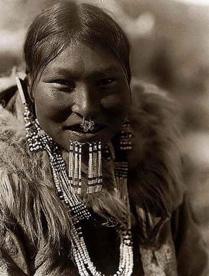 A - YUPIK NUNIVAK - Mujer - Entre los YN las mujeres se adornaban con labrets con largas sartas de cuentas de marfil, además de colgantes nasales, pendientes y collares - ES Curtis - 1930.jpg