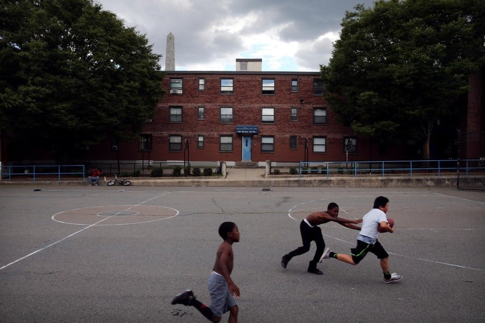 CRAIG F. WALKER/GLOBE STAFF  Jewelz Riley, 8, and his brother David, 10, played football in Bunker Hill with Evan Yang, 10.
