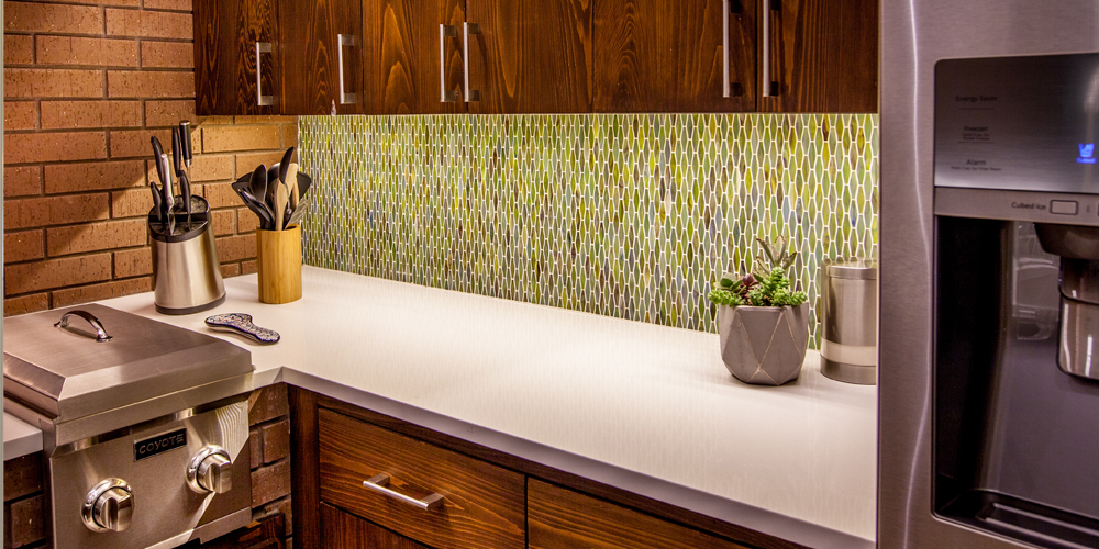 The color, shape, and mosaic nature of this tile backsplash make it a standout feature in this outdoor kitchen.