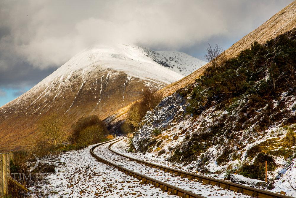 Snowy railroad past Beinn a Chaisteil and Beinn Dorain