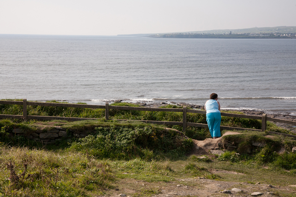 A documentary photograph of a woman looking out at the sea in the west of ireland