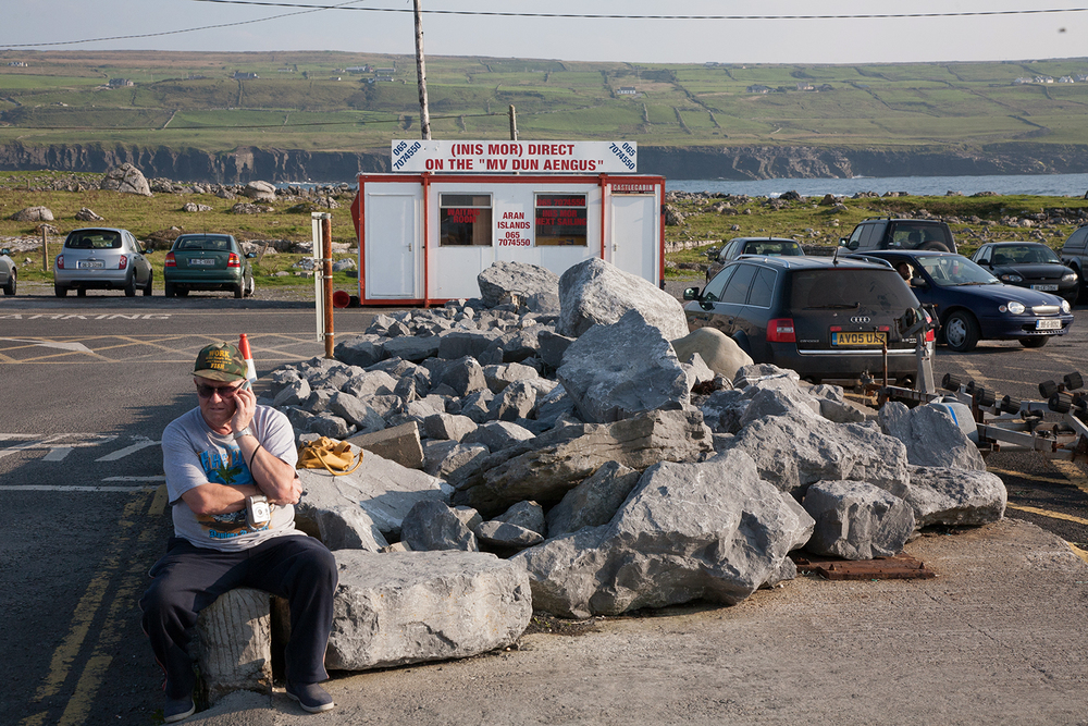 A documentary photograph of a man waiting for the ferry to the Aran Island in the West of Ireland