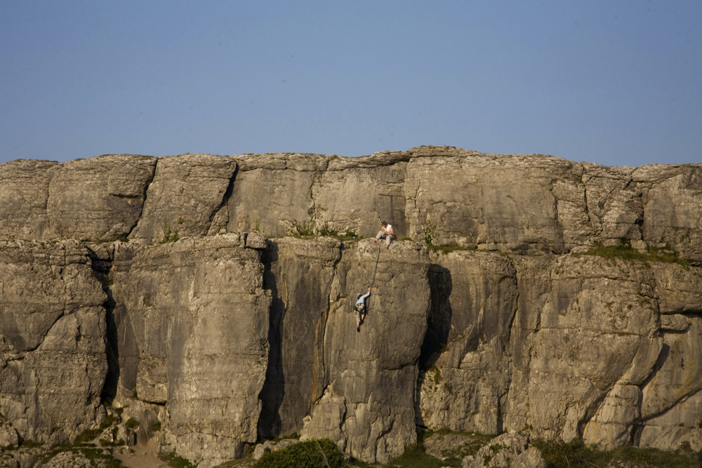 A documentary photograph of people rock climbing in the burren in the west of ireland