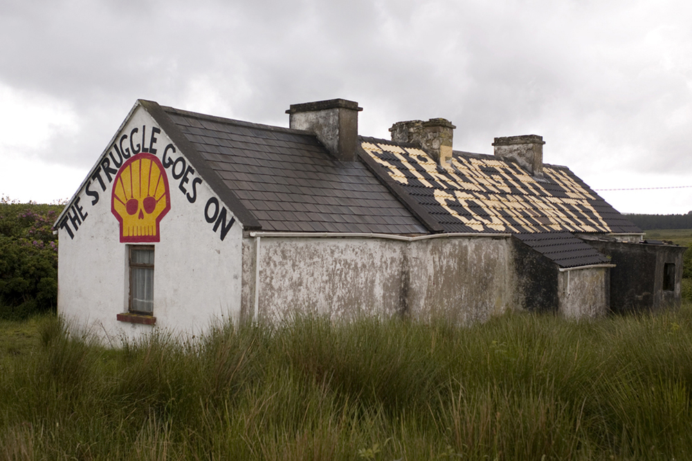 A documentary photograph of an abandoned home painted to promote the fight against shell moving into ireland