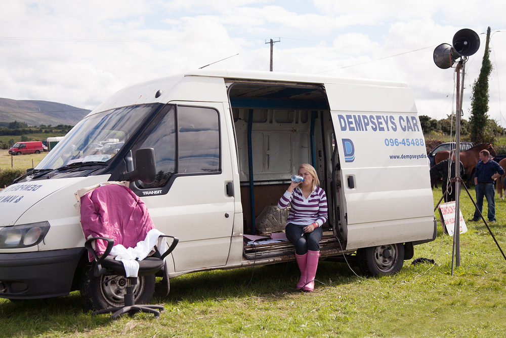 A documentary photograph of a woman drinking water in her new van at an agricultural show in the west of ireland