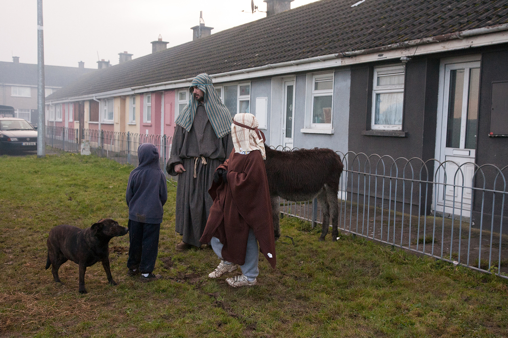 A documentary photograph of two boys, dog and donkey standing beside a man before they perform a live nativity scene in Moyross, Limerick, Ireland