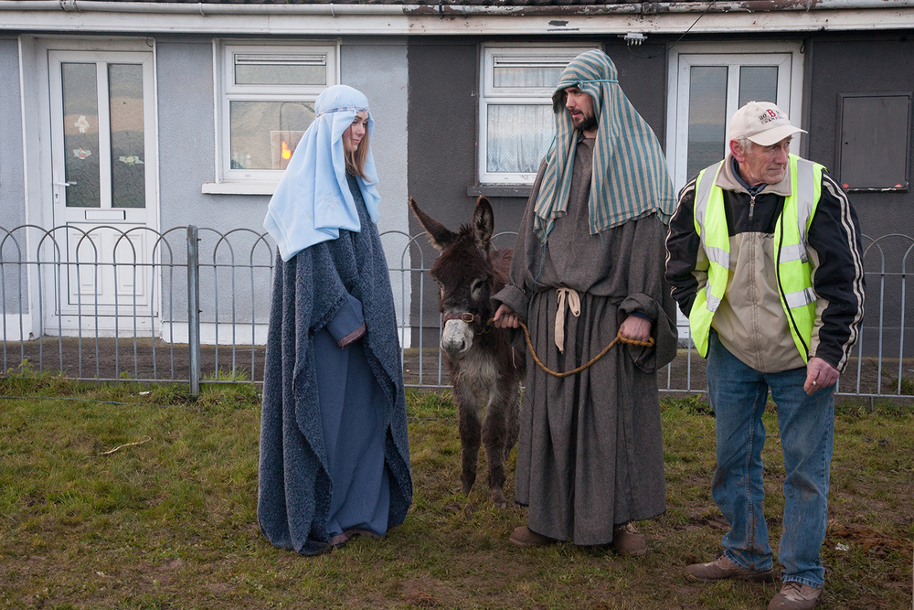 A documentary photograph of a man standing by two actors before they perform a live nativity with the monk of moires in Limerick, Ireland