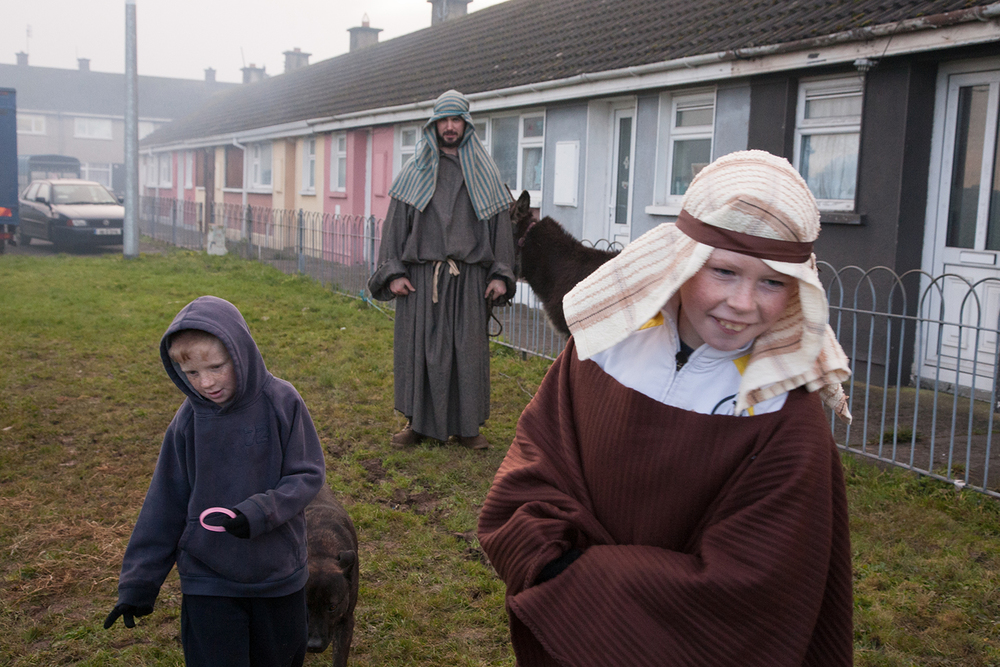 A documentary photograph of two boys walking away from a man and a donkey before they perform a live nativity scene with the Monks of Moyross in Limerick City