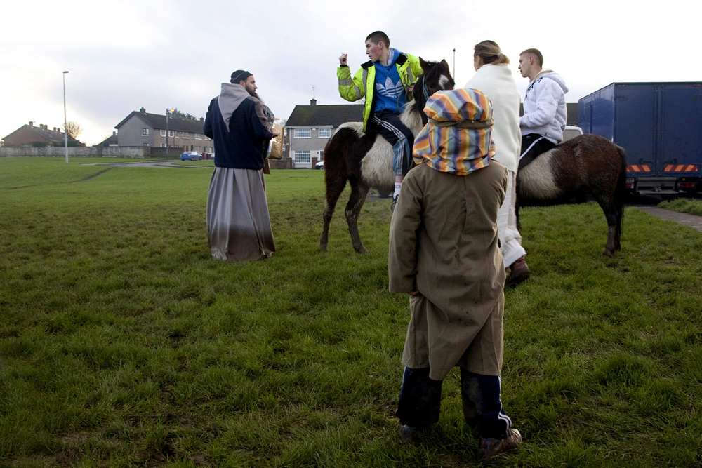 A documentary photograph of a boy watching a teenager on a horse yell at monk who is working in Moyross, Limerick, Ireland