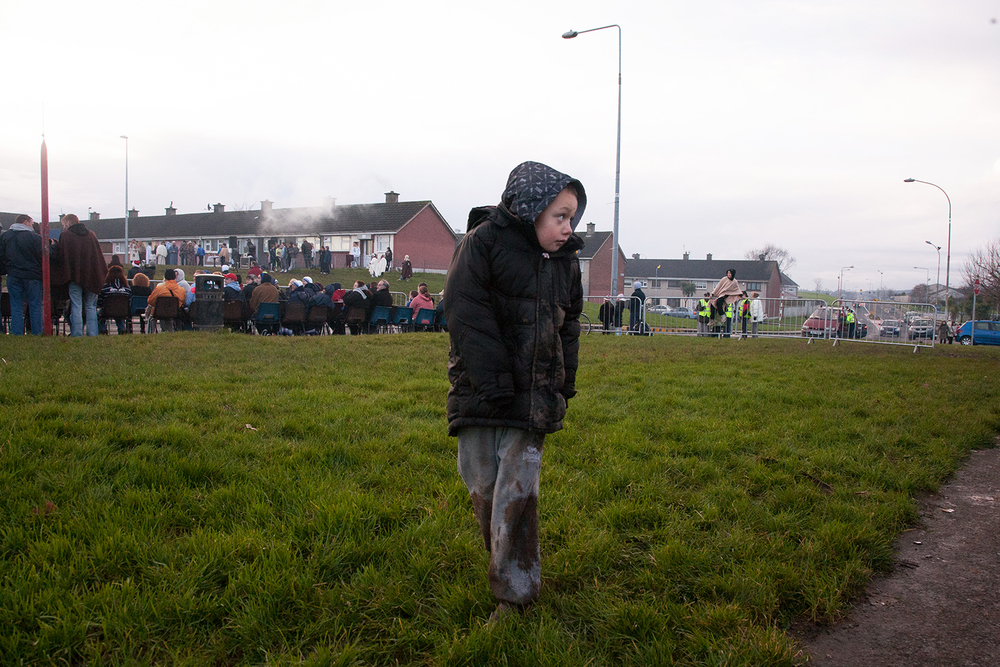 A documentary photograph of a boy walking away from the crowd as the monks perform a live nativity scene in Moyross, Limerick, Ireland
