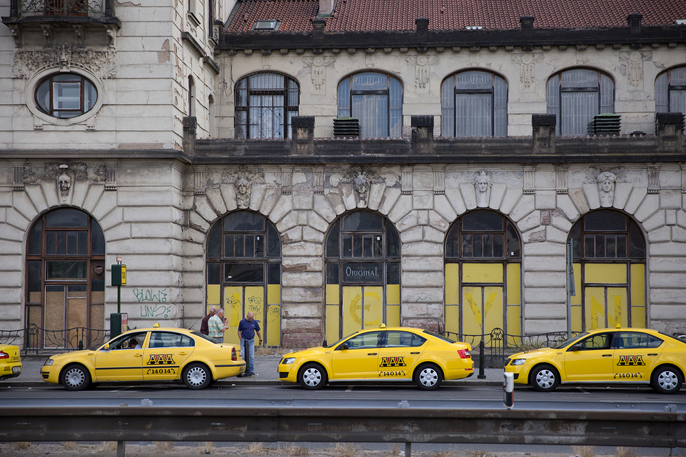 A documentary photograph of yellow taxi cabs waiting outside the train station in Prague, Czech Republic