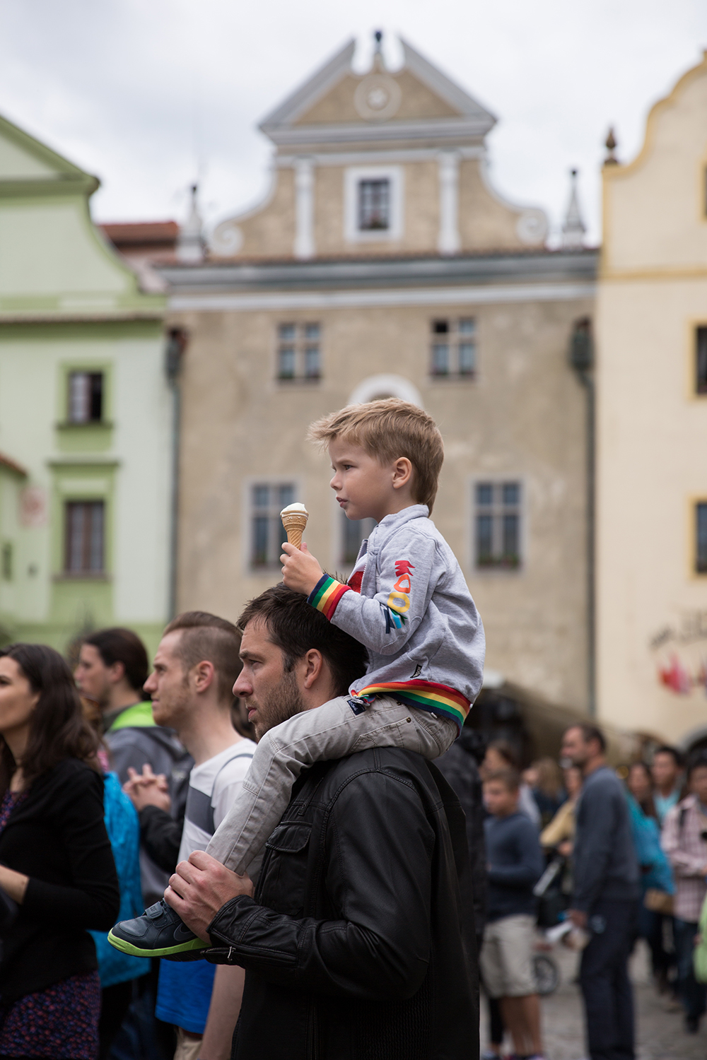 A documentary photograph of a child eating an ice cream cone on his dad's shoulders during a festival in Cesky Krumlov, Czech Republic