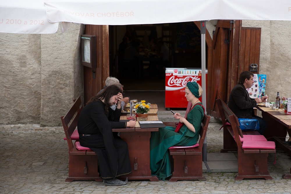 A documentary photograph of two cesky krumlov residents eating lunch and texting while wearing costumes from historical time in Czech Republic
