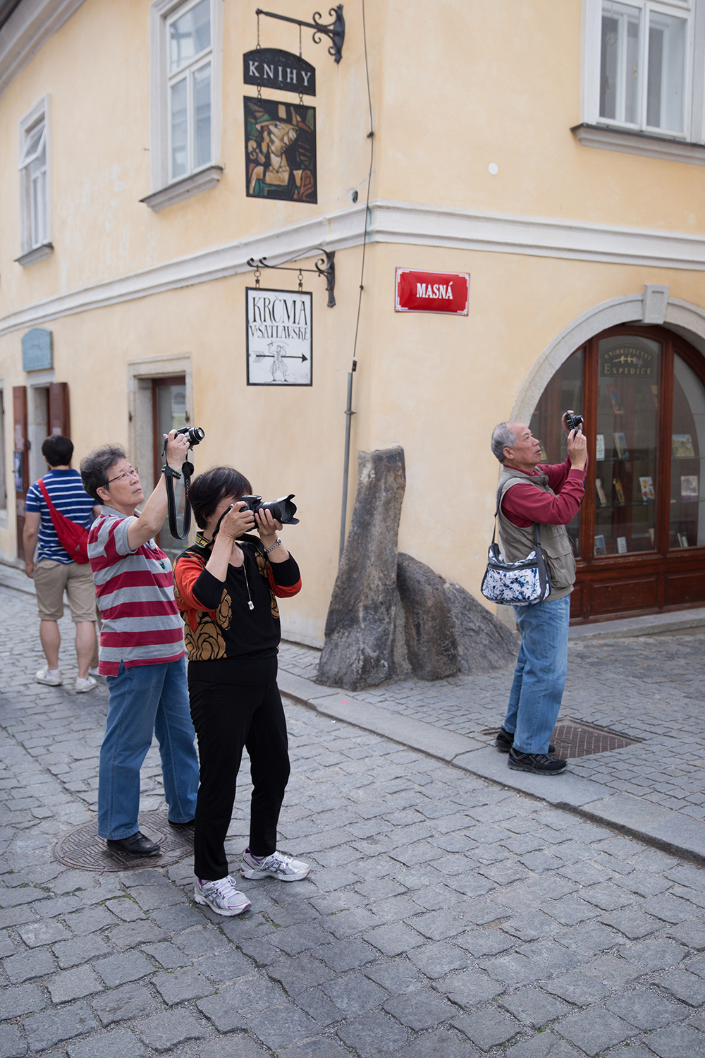 A documentary photograph of tourist taking photographs in the streets of cesky krumlov, czech republic