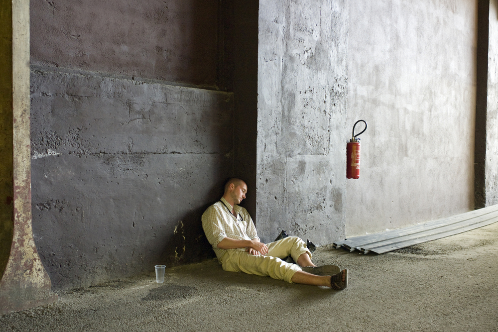 A documentary photograph of a man sleeping against the wall of an warehouse building in europe