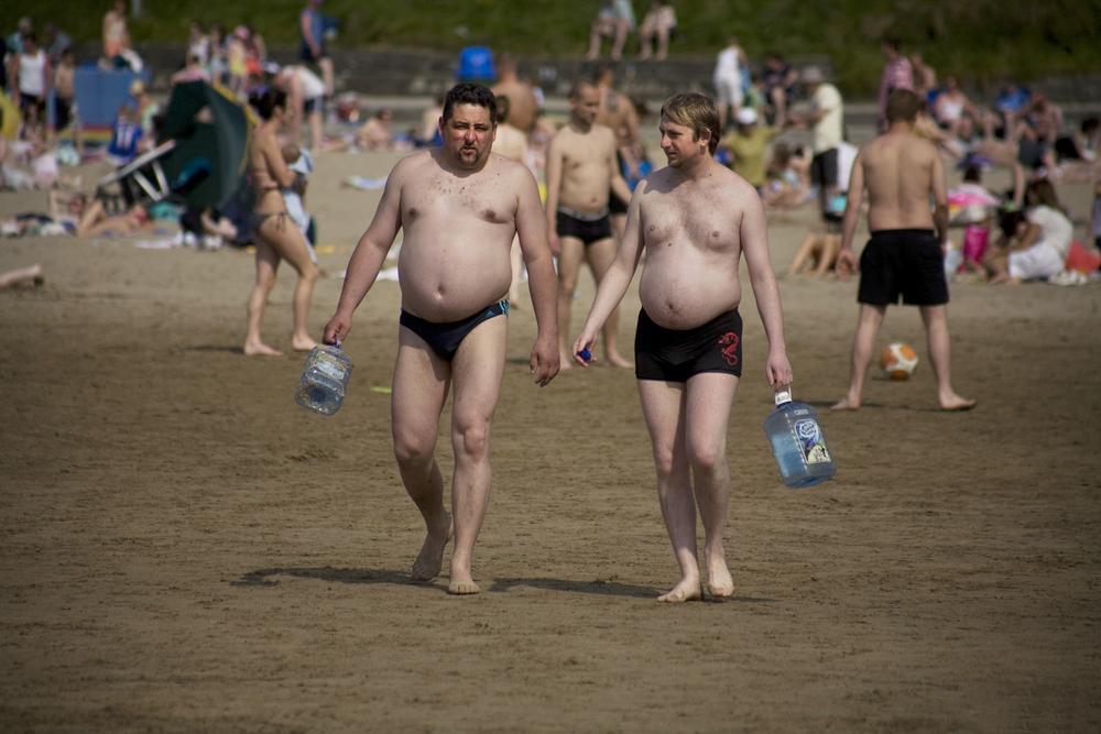 A documentary photograph of two men walking along an irish beach holding empty water jugs