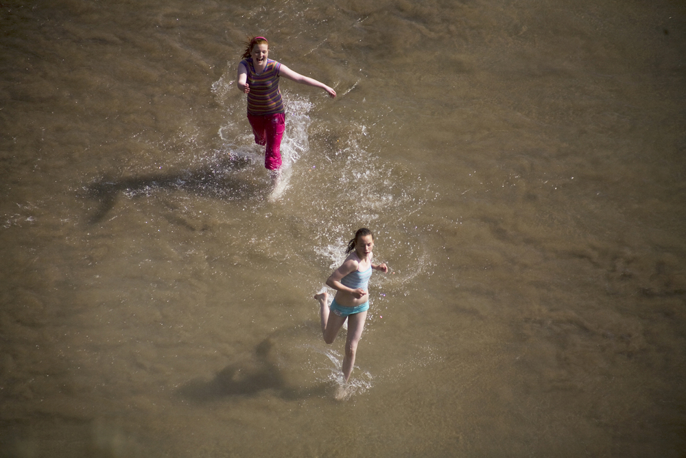 A documentary photograph of two girls running on an irish beach during a rare heat wave