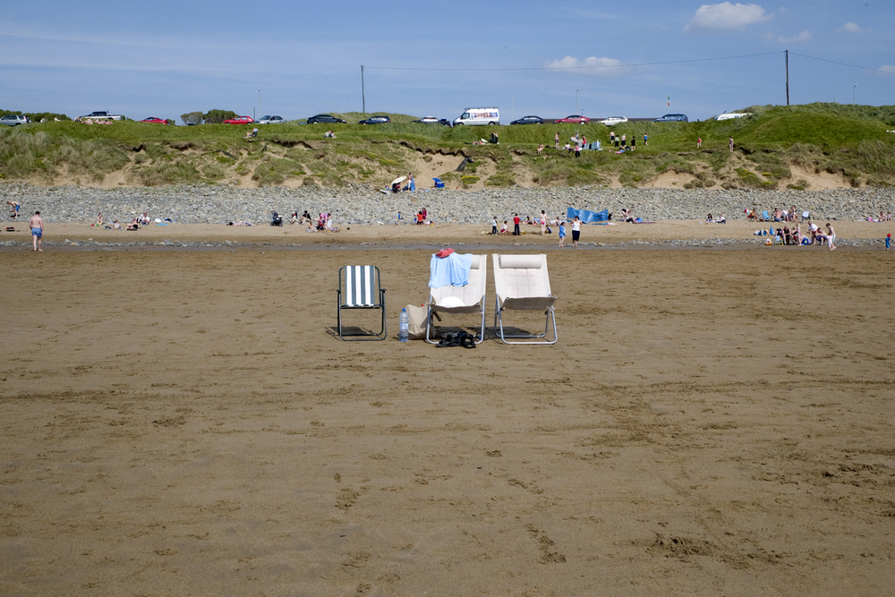 A documentary photograph of lawn chairs on the beach in Ireland