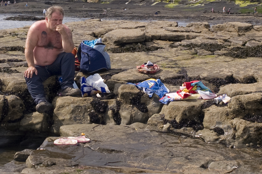 A documentary photograph of a tattooed man sitting on rocks at an irish beach with his shirt off