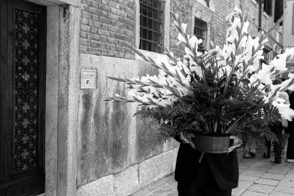 A documentary photograph of a person walking with flowers through the street of italy