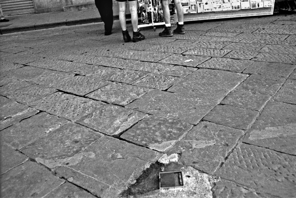 A documentary photograph of two men wearing boots looking at postcards in italy